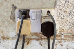 Wall socket overloaded with adapters and plugs